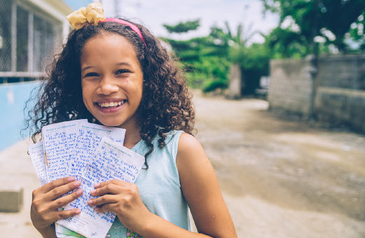 A girl displays letters of hope from her sponsor, which she treasures.